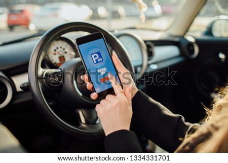 Woman in car. Girl using smartphone app to pay for the parking. #1334331701