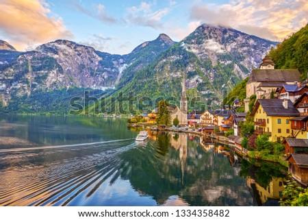 Amazing Sunset in Hallstatt  - mountain village with Hallstatter lake and boat in Austrian Alps.  #1334358482