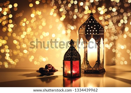 Ornamental Arabic lanterns with burning candles. Glittering golden bokeh lights. Plate with date fruit on the table. Greeting card for Muslim holiday Ramadan Kareem. Iftar dinner background. #1334439962