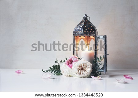 Vintage silver Moroccan, Arabic lantern with glowing candle, green branches, rose flowers and pink petals on white table background. Greeting card for Muslim holiday Ramadan Kareem. Shaby wall. #1334446520