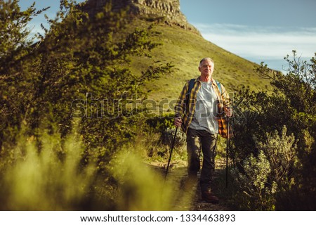 Senior man trekking down a hill holding trekking poles. Man holding hiking poles walking down a hill wearing backpack. #1334463893