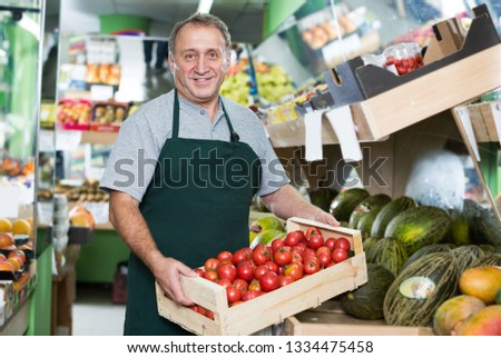 Positive man employee showing box with natural tomatos in the hypermarket #1334475458