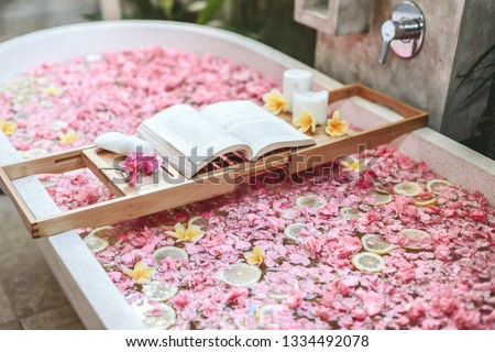 Bath tub with flower petals and lemon slices. Book and candles on a tray. Organic spa relaxation in luxury Bali outdoor bathroom. #1334492078