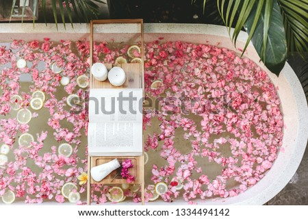 Top view of bath tub with flower petals and lemon slices. Book, candles and beauty product on a tray. Organic spa relaxation in luxury Bali outdoor bathroom. #1334494142