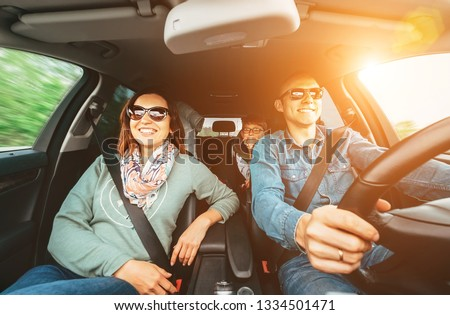 Young traditional family has a long auto journey and Cheerfully singing aloud the favorite song together. Safety riding car concept wide angle inside car view image. #1334501471