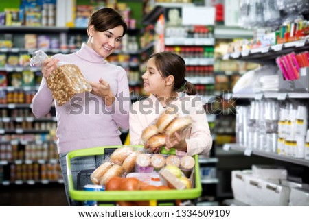 Smiling female shopper with teenage daughter searching for bread in supermarket #1334509109