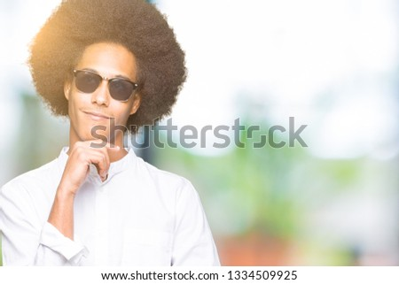 Young african american man with afro hair wearing sunglasses with hand on chin thinking about question, pensive expression. Smiling with thoughtful face. Doubt concept. #1334509925
