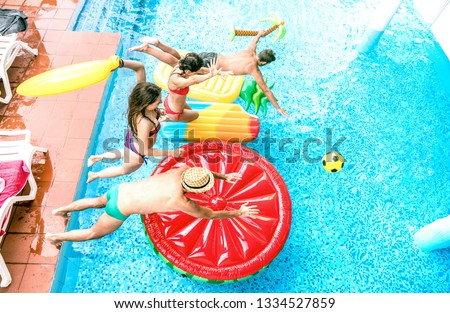 High angle view of millenial friends jumping at swimming pool party - Youth vacation concept with happy guys and girls having fun in summer day at luxury resort - Young people on warm bright filter #1334527859