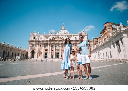 Happy family at St. Peter's Basilica church in Vatican city. Travel parents and kids on european vacation in Italy.