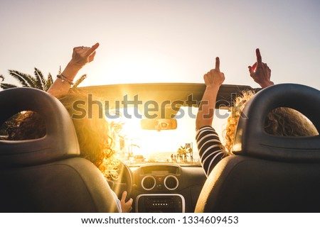Couple of woman friends traveling and driving having a lot of fun dancing in the car with opened roof and summer vacation sunset ocean in front - concept of friendship together and nice lifestyle  #1334609453