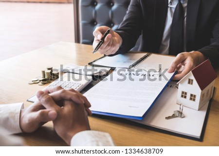 Estate agent broker giving pen to client signing agreement contract real estate with approved mortgage application form, buying or concerning mortgage loan offer for and house insurance. #1334638709