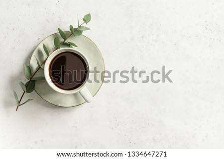 Cup of black coffee on a white textured table with a branch of eucalyptus. Top view, minimalism style, copy space.