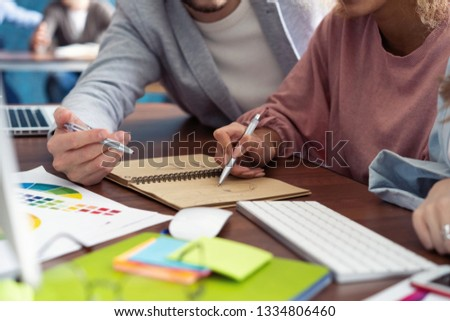 Young woman working at her desk taking notes. Focus on hand writing on a notepad. #1334806460