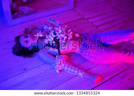 A girl with flowers is lying on the floor, with a red, blue neon lamp. Photo session on a neon background #1334855324