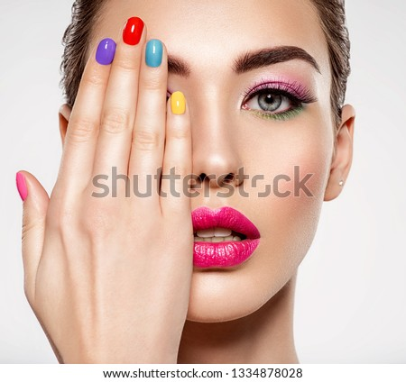 Beautiful fashion woman with a colored nails. Attractive white girl with multicolor manicure. Glamour fashion model with bright gloss make-up posing at studio. Stylish fashionable concept. Art #1334878028