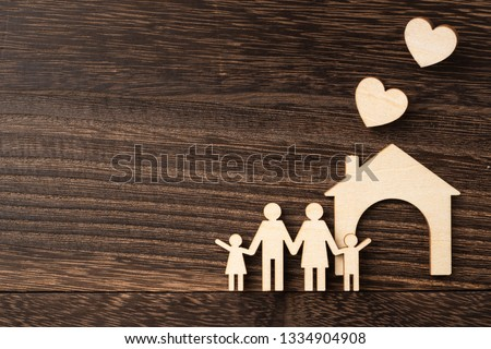 family and design concept - wooden family piece on dark wood background. it's love, protect and secure concept
