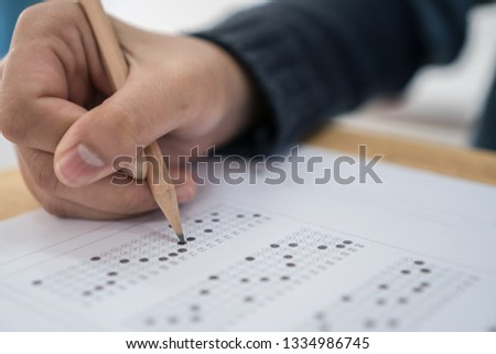 Students hands taking exams, writing examination room with holding pencil on optical form of standardized test with answers and english paper sheet on row desk chair doing final exam in classroom. #1334986745