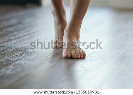 Feet walking on heated floor - wood or vinyl. Royalty-Free Stock Photo #1335010931