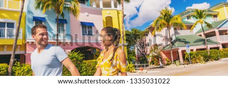 Summer florida vacation couple walking in city street with colorful beach houses wooden cottages at Fort Myers Beach traditional color house - panoramic banner.