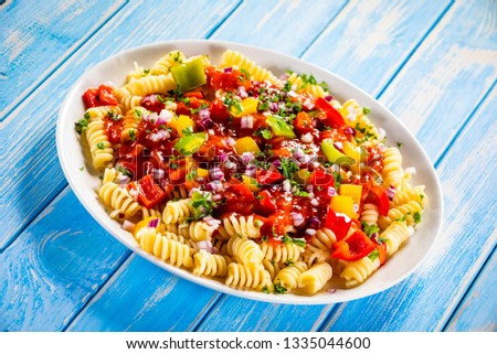 Pasta with vegetables on wooden background #1335044600