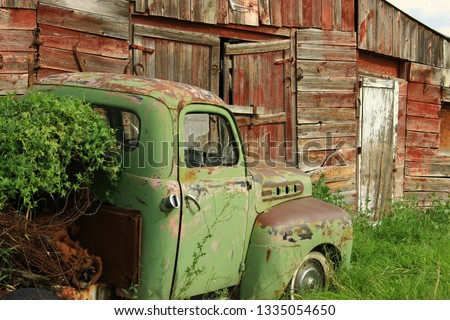 Old Chevy truck in front of old red barn #1335054650