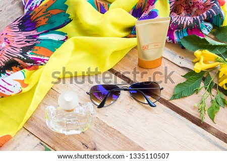 accessories cosmetics health care skin face sunscreen spf50 with yellow scarf ,sunglasses ,perfume of lifestyle woman relaxation in summer arrangement on background wooden  #1335110507