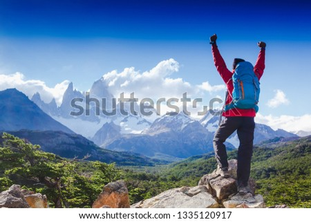 hiker celebrating success on top of a mountain in a majestic Patagonia mountain landscape. Fitz Roy, Argentina. Mountaineering sport lifestyle concept #1335120917