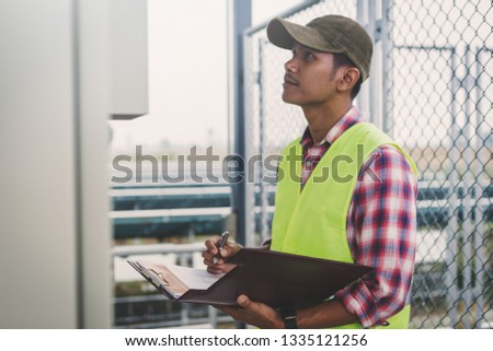 engineer or electrician inspect and checking solar equipment ;smart technology for operation of solar power plant by smart operator #1335121256