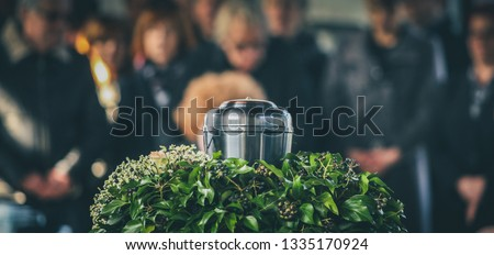 Panoramic photo of metal urn with ashes of dead person on funeral, with people mourning in background on memorial service. Sad grieving moment at end of life. Last farewell to a person in urn. #1335170924