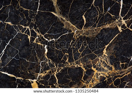 A slab of black marble with beautiful yellow streaks is called New Portoro #1335250484