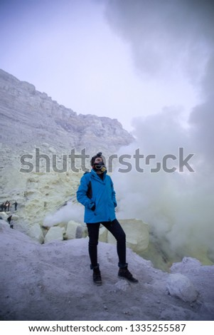 Young portrait wearing gas mask at biggest crater lake volcano of Kawah Ljen in east java, Indonesia #1335255587