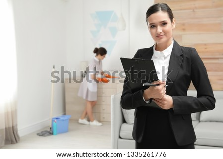 Housekeeping manager checking maid work in hotel room #1335261776