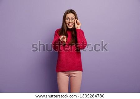 Teenage girl with happy expression indicates directly at camera, points with fore finger, greets friend, wears optical glasses and red jumper, isolated over purple studio wall, invites guests, hints #1335284780