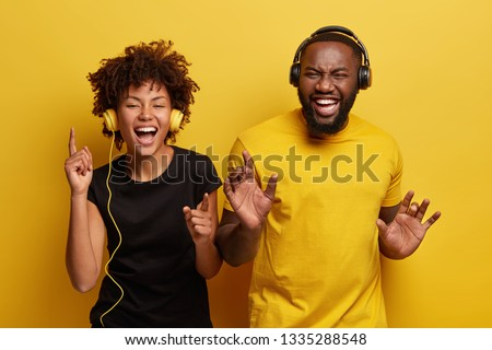 Indoor shot of overemotive girlfriend and boyfriend with dark skin never leave home without headphones, cant imagine life with no music, dance happily, isolated over yellow studio background. #1335288548