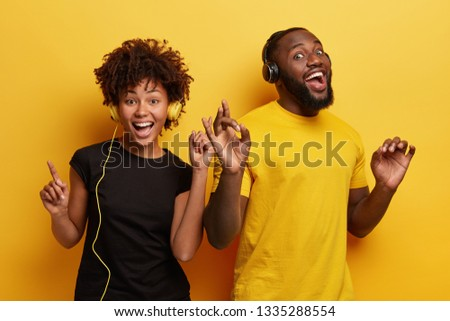 Happy friends pick track in app, listen awesome song, makes okay gesture, point with fingers while dance, feels carefree and relaxed during awesome party, stand next to each other over yellow wall #1335288554