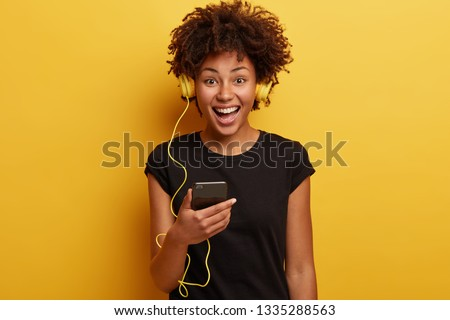 Time for listening music and entertainment. Friendly looking sincere positive woman holds modern cell phone, enjoys great sound in headphones, sing aloud, dressed in black t shirt, yells happily #1335288563