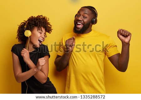 Cheerful young African American bloggers enjoy favourite playlist in headphones, listens audio in music app, feels happiness, dance actively against yellow background, move emotionally, have fun #1335288572