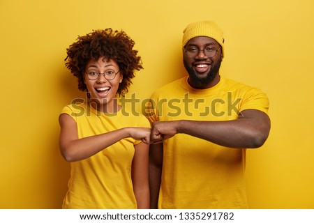 Studio shot of overjoyed satisfied woman and man with dark skin, give fist bump, agree to work together, have success in project work, wear yellow attire, pose in studio. Cooperation concept #1335291782