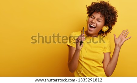 Yeah, I am pleased. Joyful lovely dark skinned woman raises hand in dance move, likes great sound in new headphones, sings loudly, carries cellular, smiles broadly, wears yellow casual clothes #1335291812
