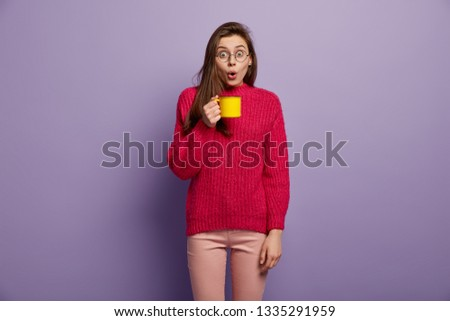 Stupefied shoolgirl drinks hot beverage from yellow cup, amazed to hear shocking news about friends, has coffee break after classes, wears round glasses and red jumper, isolated over purple wall #1335291959
