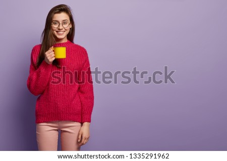 Studio shot of cheerful young lady holds yellow mug of hot drink, enjoys coffee or tea, smiles positively, dressed in casual clothes, models over purple wall, copy space for your advertisement #1335291962