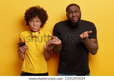 Questioned dark skinned female and male gesture with hesitation, dont know which track to choose for listening, holds smartphone, wears black and yellow t shirt, have clueless facial expressions #1335293924