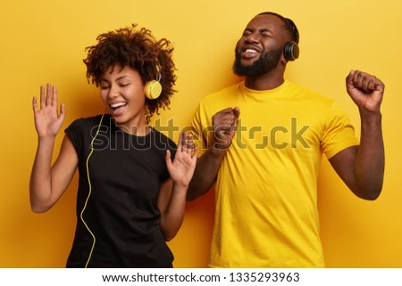 Photo of joyful positive ethnic female and male teenagers sing from pleasure, gesture actively, listen music from playlist, enjoy perfect sound, stand next to each other, isolated over yellow wall #1335293963