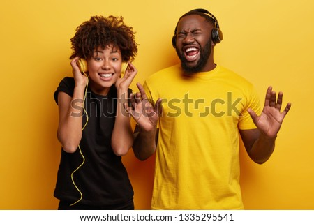 Inspired Afro American couple inspired by good music, listen popular song in headphones, smile broadly, dance energetically, feel rebellious. Its time to rock this party. Yellow bright background #1335295541