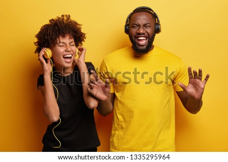 Emotional bearded dark skinned guy in yellow t shirt stands next to girlfriend, listen different musical compositions in headphones not distrub anyone with noise, have nice memories from song #1335295964