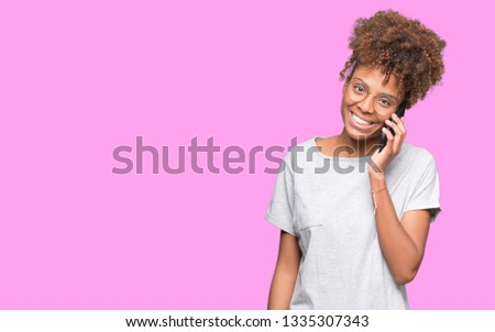 Young african american woman talking on smartphone over isolated background with a happy face standing and smiling with a confident smile showing teeth #1335307343