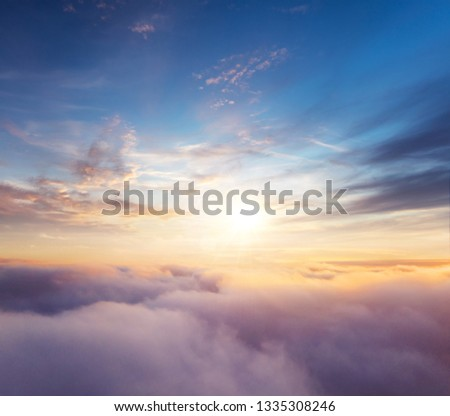 Beautiful sunset cloudy sky from aerial view. Airplane view above clouds #1335308246