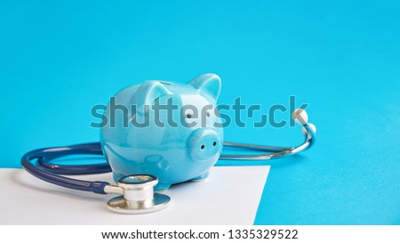 Piggy bank with stethoscope isolated on blue background. tax offset concept. Medical Expense Deductions and Tax Breaks #1335329522