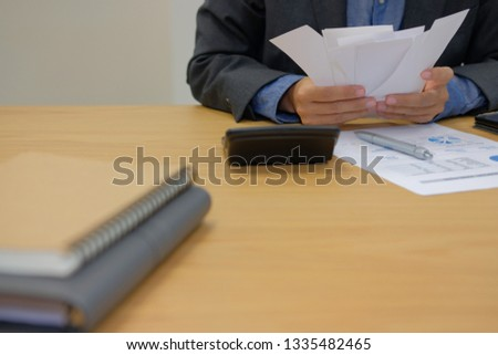 man calculate domestic bills. Businessman with calculator checking balance & costs. Startup counting finance for paying taxes at office #1335482465
