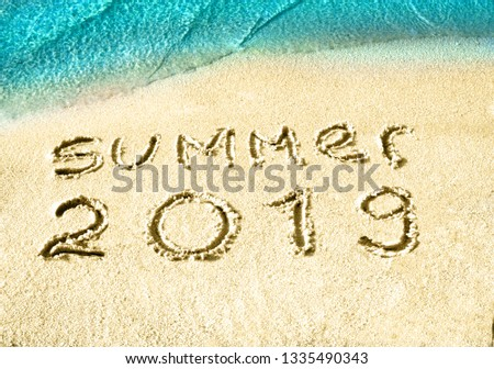 Summer 2018 nand drawn letters on white sand with blue sea paradise beach. Creative typography for Holiday Greeting Gift Poster #1335490343